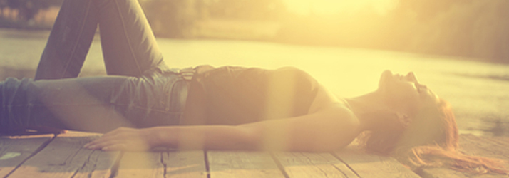 Woman Laying On A Dock In The Sun